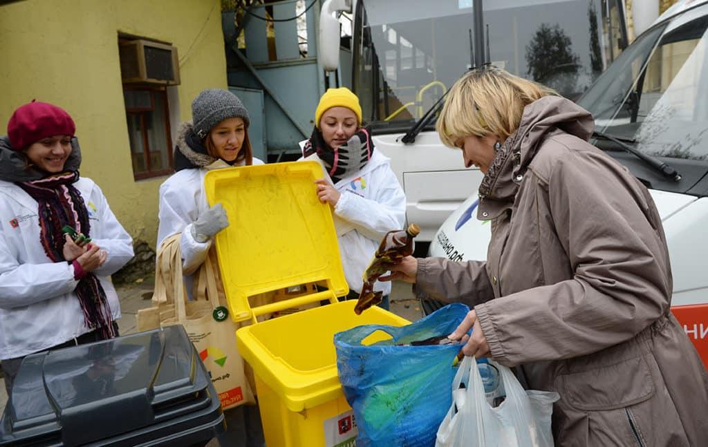 Женщина выбрасывает мусор в контейнер