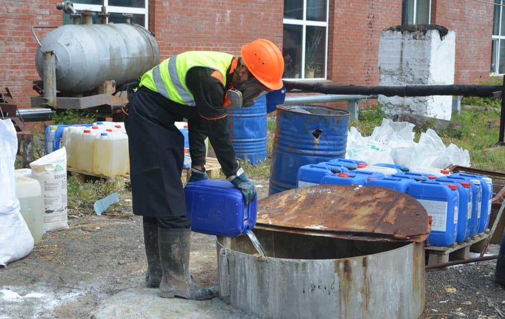 Сотрудник сливает отходы из канистры
