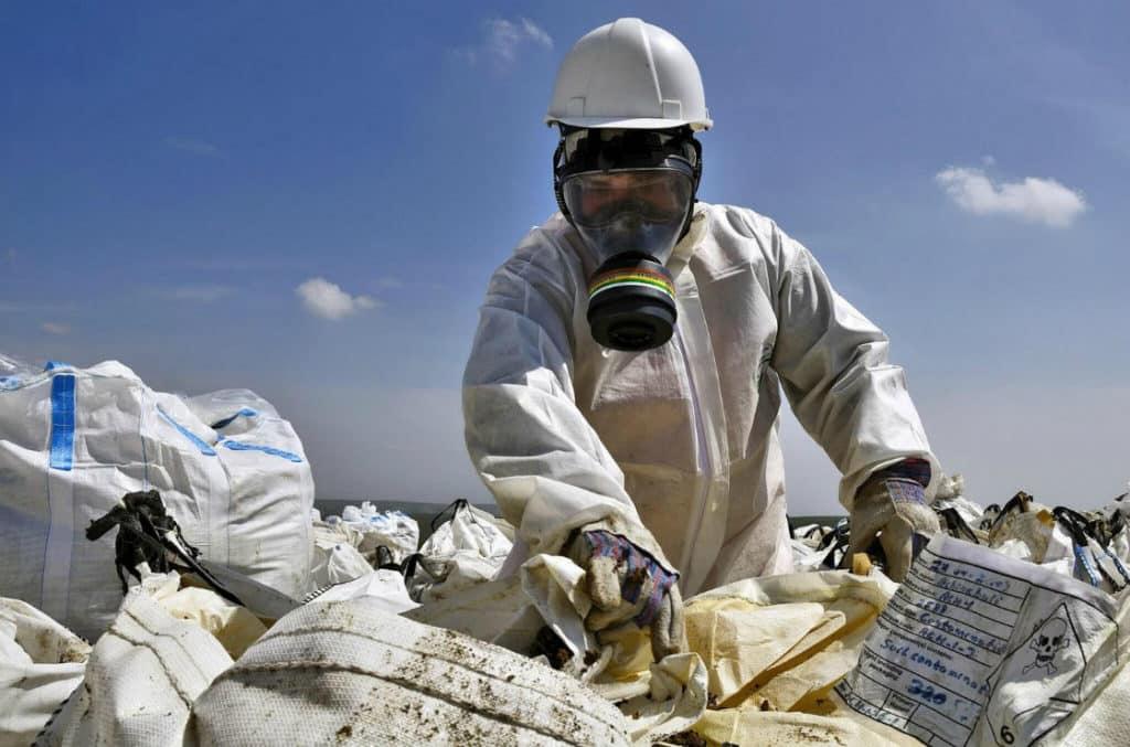 Работник в противогазе разбирает отходы